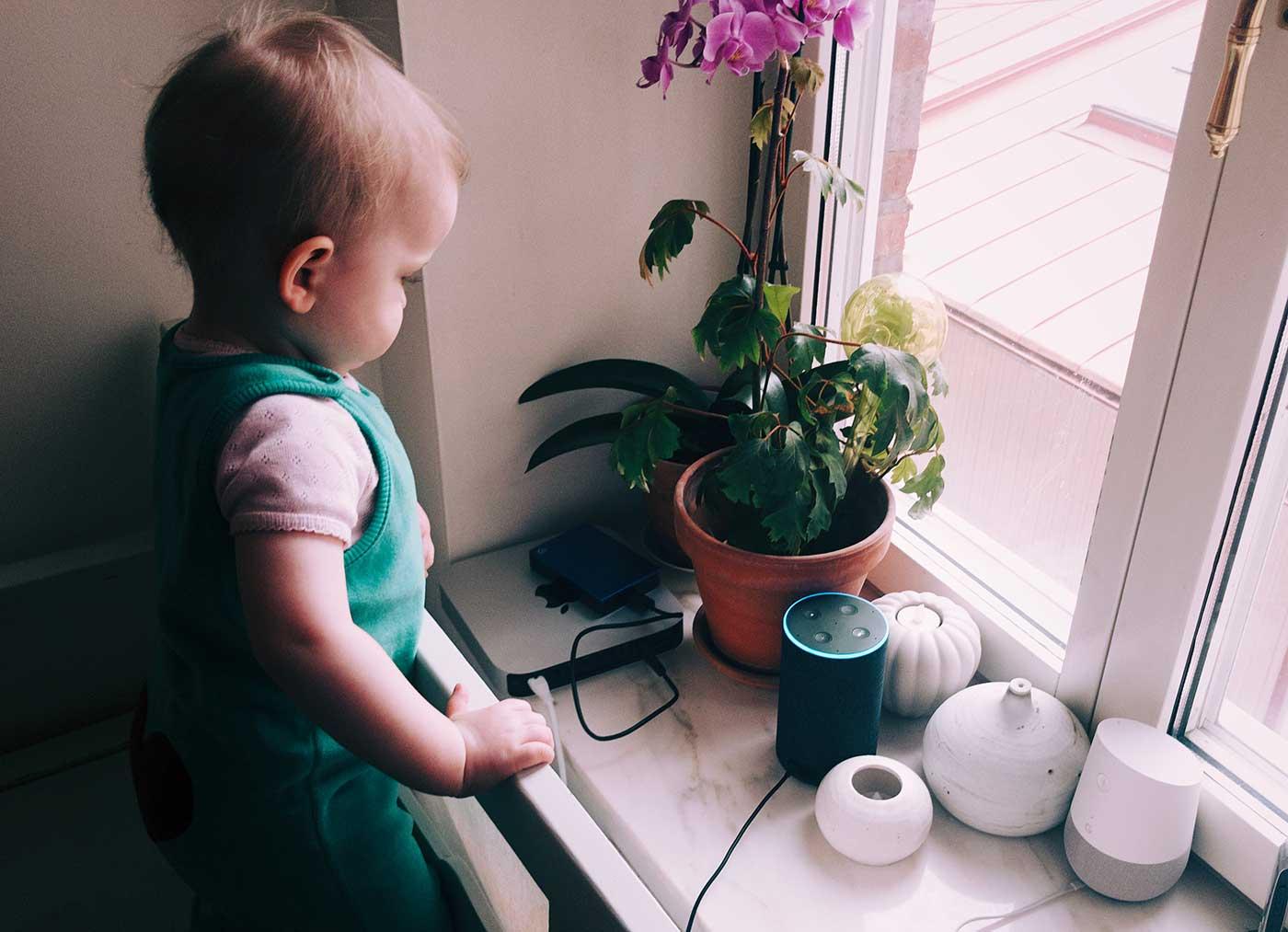 Barn bredvid Amazon Echo (Alexa), Google Home och en Apple Mac Mini